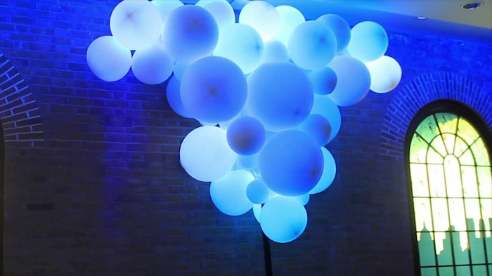 White Balloons In Blue Lightings Floating In Air.