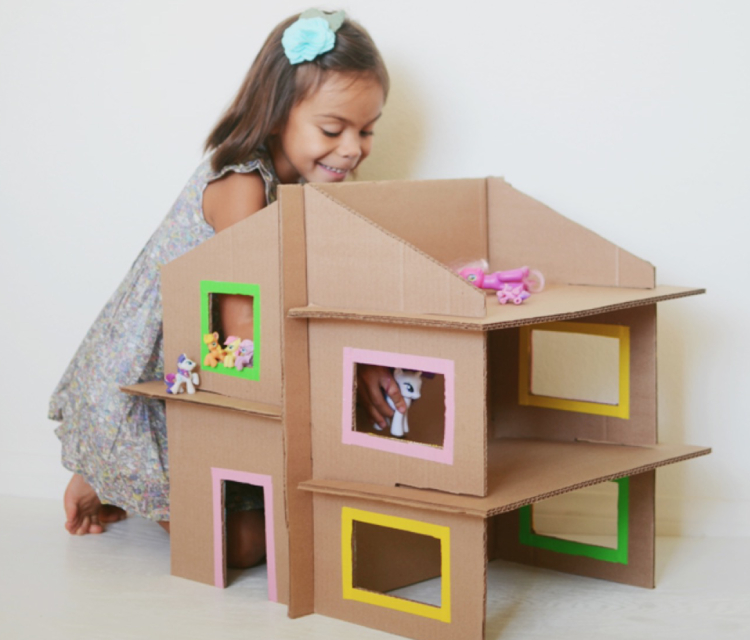 A Little Girl Doing DIY Cardboard Box Home.
