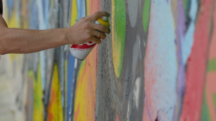 A Human Hand Hold Sprayer - Spray Painting On Wall.