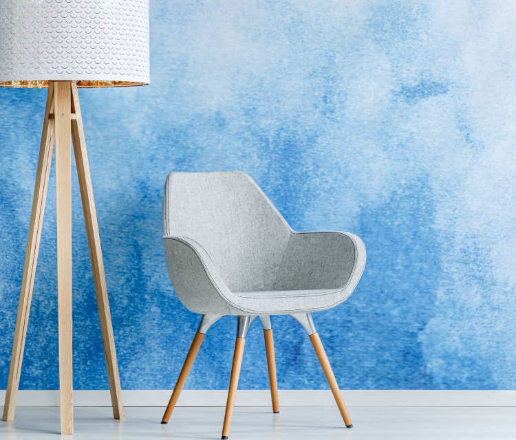 A Chair Placed Infront Of The Wall Painted By Blue Color.